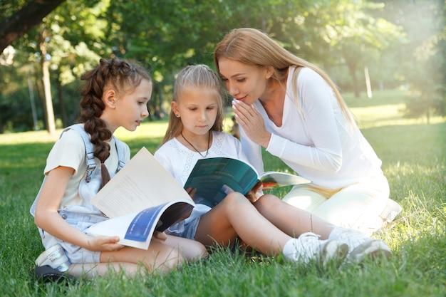 Mooie vrouwelijke leraar fluistert iets tegen haar kleine student tijdens het lezen van een boek in het park