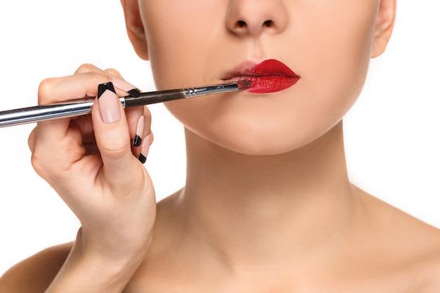 Mooie vrouwelijke lippen met make-up en penseel op wit. make-up artiest werkproces
