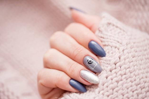 Mooie vrouwelijke manicure op een zachte sweater.