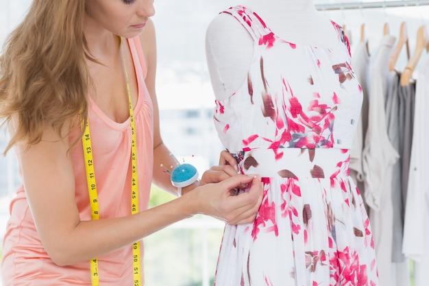Mooie vrouwelijke manierontwerper die aan bloemenkleding werkt