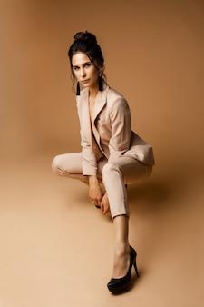 Mooie vrouwelijke mannequin met donker haar in pak vormt voor de camera