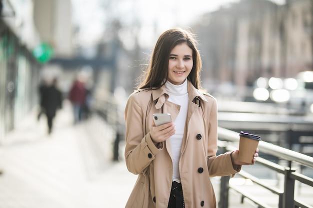 Mooie vrouwelijke model koffie drinken in groot winkelcentrum