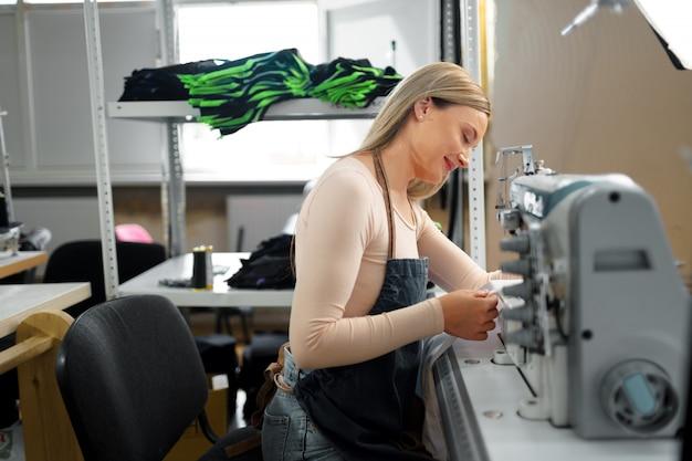 Mooie vrouwelijke naaister werken met stof op haar werkplek