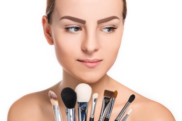 Mooie vrouwelijke ogen met make-up en borstels op wit