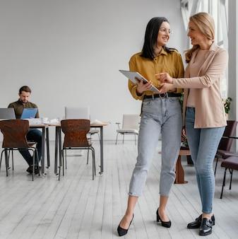Mooie vrouwelijke ondernemers praten met kopie ruimte
