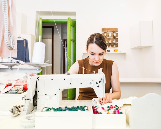 Mooie vrouwelijke ontwerper naaiende stof op naaimachine