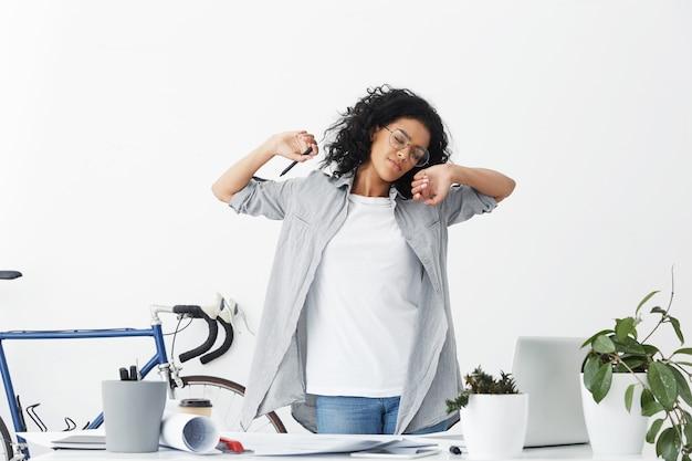 Mooie vrouwelijke ontwerpmedewerker met volumineus donker haar dat een casual shirt draagt en moe wordt