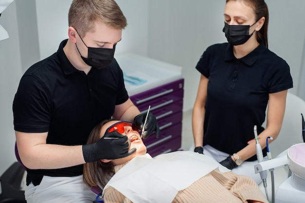 Mooie vrouwelijke patiënt in rode beschermende bril in een tandheelkundige stoel bij moderne stijlvolle kliniek.