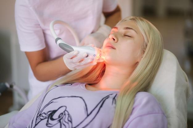 Mooie vrouwelijke patiënt krijgt een behandeling van de gezichtshuid terwijl hij in de medische kliniek ligt.
