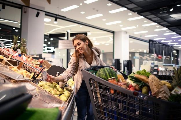 Mooie vrouwelijke persoon die de prijs van fruit bij kruidenierswinkelopslag controleert