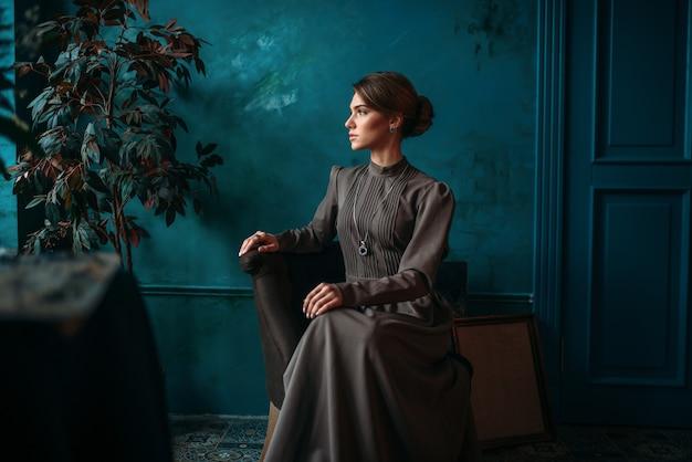 Mooie vrouwelijke poseur in jurk zittend op een stoel in art studio.