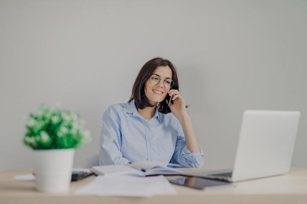 Mooie vrouwelijke recruiter doet jobaanbieding aan somene via mobiele telefoon, controleert curriculum vitae op laptopcomputer