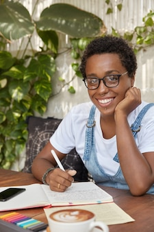 Mooie vrouwelijke redacteur werkt aan boekbespreking, schrijft idee in notitieblok