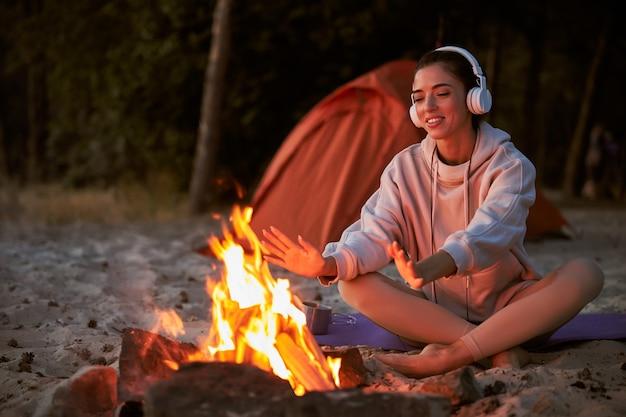Mooie vrouwelijke reiziger die handen bij het vuur verwarmt en glimlacht terwijl hij naar muziek luistert via een draadloze hoofdtelefoon