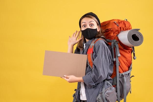 Mooie vrouwelijke reiziger met zwart masker en rugzak met karton