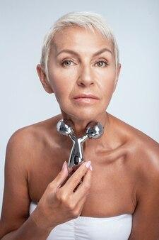 Mooie vrouwelijke rollende gezichtsmassager van middelbare leeftijd op haar nek