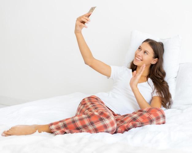 Mooie vrouwelijke selfie, blonde neemt foto op mobiele telefoon tot in bed en zwaaiende hand. mooie vrouw en lachend, liefde voor jezelf.