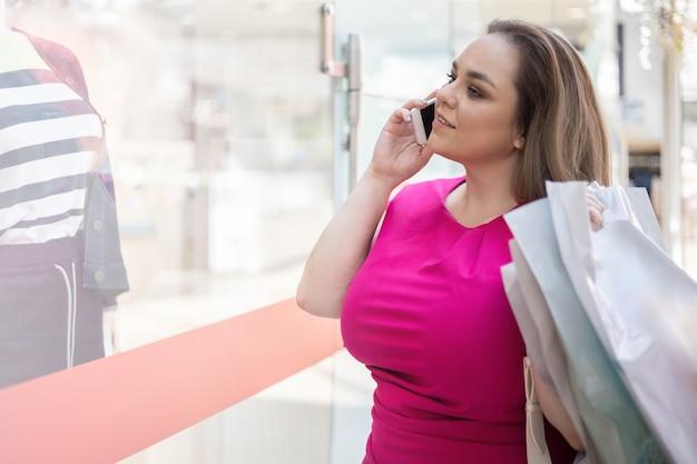 Mooie vrouwelijke shopaholic die naar de showcase van de modeboetiek kijkt met papieren boodschappentassen