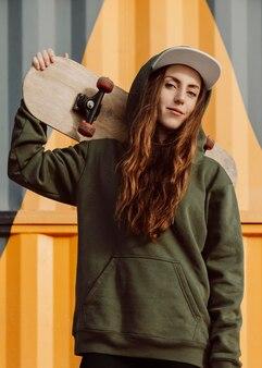 Mooie vrouwelijke skater die haar skateboard vooraanzicht houdt