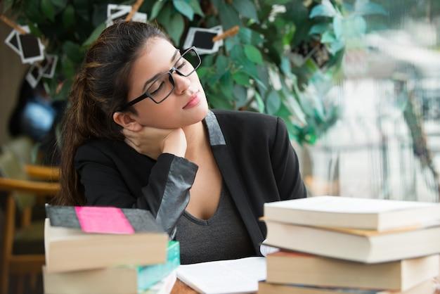 Mooie vrouwelijke student aan tafel aan tafel met boeken