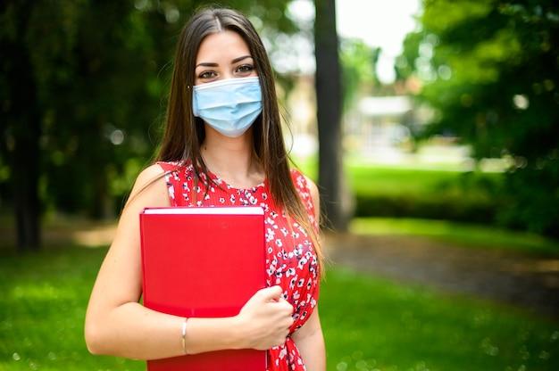 Mooie vrouwelijke student die een boek buiten houdt en een masker draagt, coronavirusconcept