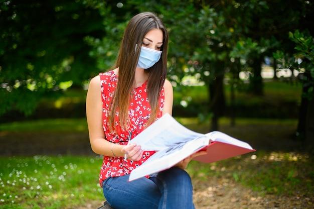 Mooie vrouwelijke student die een boek op een bank in een park leest en een masker draagt in coronavirus tijden
