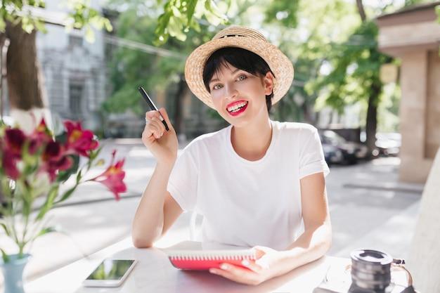 Mooie vrouwelijke student die in tuin met notitieboekje en pen koelen die bloemsmaak geniet