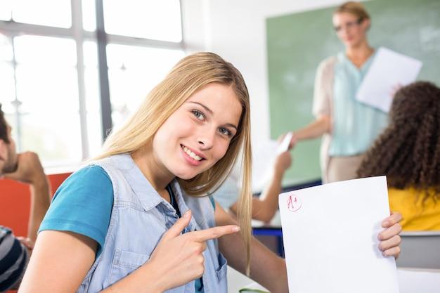 Mooie vrouwelijke student die op papier richt
