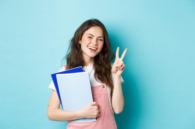 Mooie vrouwelijke student die v-teken toont en gelukkig glimlacht, notitieboekjes met studiemateriaal vasthoudt, cursussen bijwoont, over blauwe achtergrond staat.