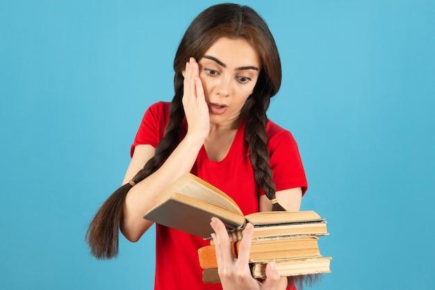Mooie vrouwelijke student in rood t-shirt leesboek met geschokte uitdrukking.