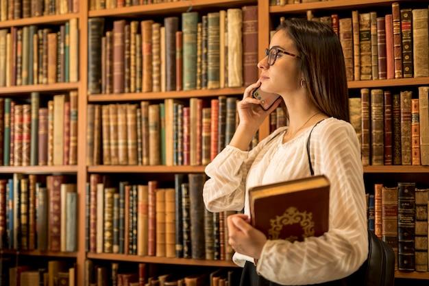 Mooie vrouwelijke student met boeken die op telefoon in bibliotheek spreken
