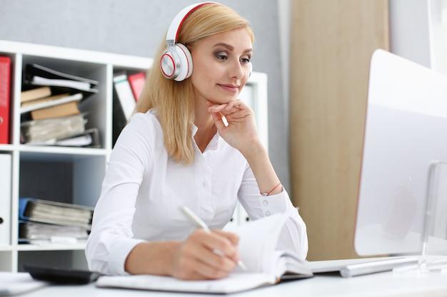 Mooie vrouwelijke student met koptelefoon luisteren naar muziek en leren.