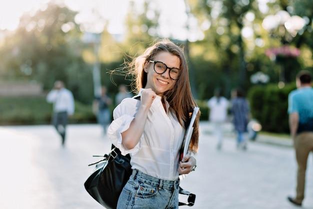 Mooie vrouwelijke student met rugzak en boeken buitenshuis.