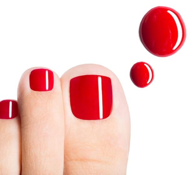 Mooie vrouwelijke tenen met rode pedicure en druppels nagellak over witte ruimte