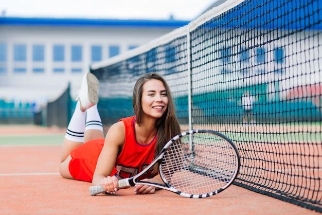 Mooie vrouwelijke tennisspeelster op de tennisbaan in rode jurk.