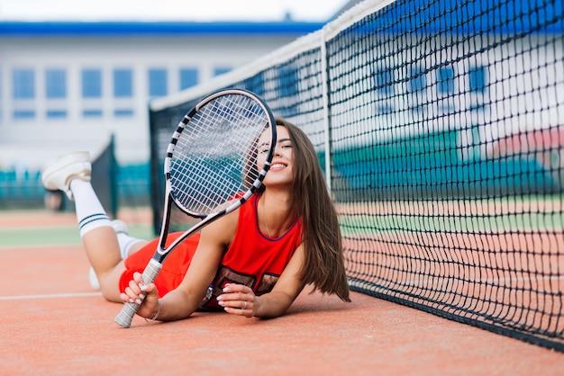 Mooie vrouwelijke tennisspeelster op tennisbaan in rode jurk.