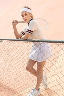 Mooie vrouwelijke tennisspeler die camera bekijkt