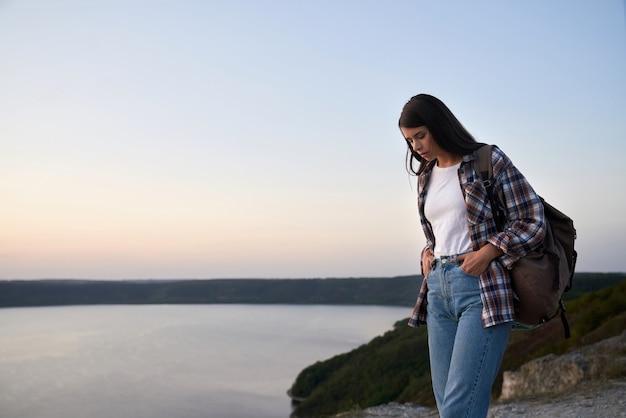Mooie vrouwelijke toerist die met rugzak op hoge heuvel dichtbij de rivier van dnjestr loopt.
