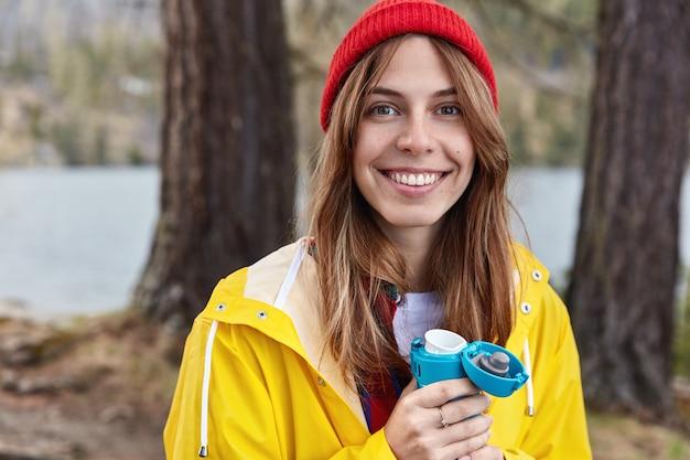 Mooie vrouwelijke toerist heeft warme drank uit thermos in voorjaar bos, draagt rode hoed en gele regenjas, glimlacht breed naar camera