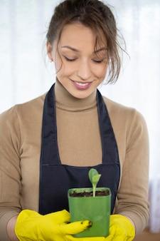 Mooie vrouwelijke tuinman houdt groene pot met microgreens groenten zaailing in handen, focus op gezicht, gelukkige jonge vrouw kijkt naar groeiende planten, moestuin, biologische producten, duurzaam tuinieren