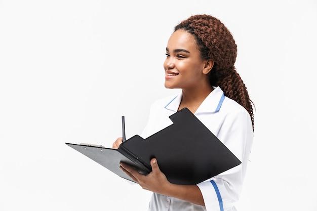 Mooie vrouwelijke verpleegster die een medisch casusrapport schrijft dat tegen een witte muur wordt geïsoleerd