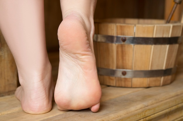 Mooie vrouwelijke voeten in sauna, badaccessoires. houten emmer