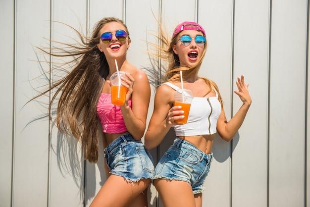 Mooie vrouwelijke vrienden met sap hebben plezier.