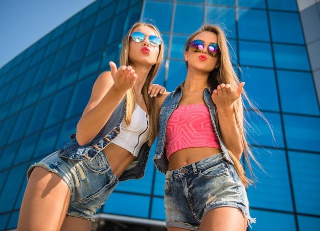 Mooie vrouwelijke vrienden poseren in de buurt van het gebouw.