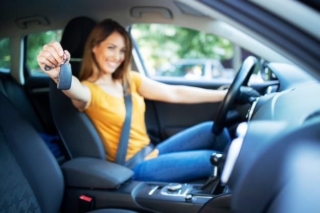 Mooie vrouwelijke vrouwenbestuurder die in haar voertuig zitten en autosleutels klaar voor een rit houden