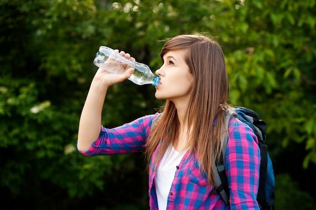 Mooie vrouwelijke wandelaar drinkwater in het bos