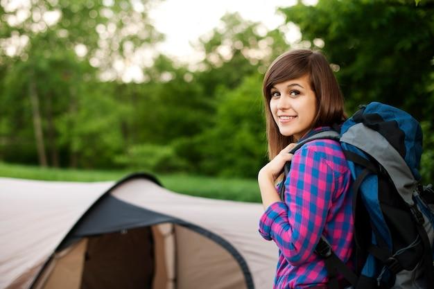 Mooie vrouwelijke wandelaar met tent