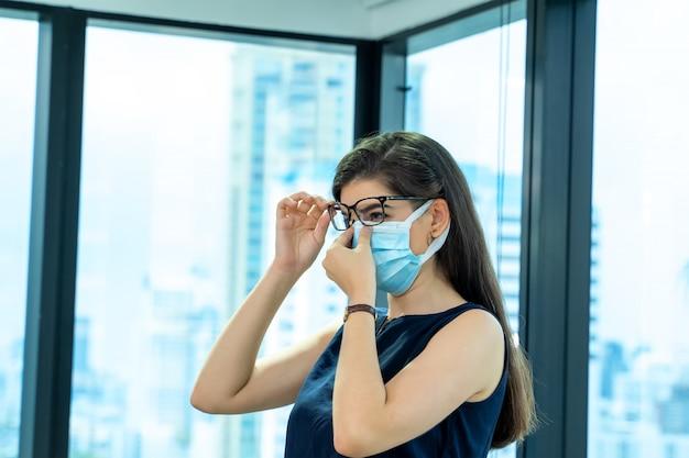Mooie vrouwelijke werknemer die medisch gezichtsmasker draagt dat alleen werkt vanaf sociaal afstandsbeleid in het bedrijfskantoor tijdens het nieuwe normaal.