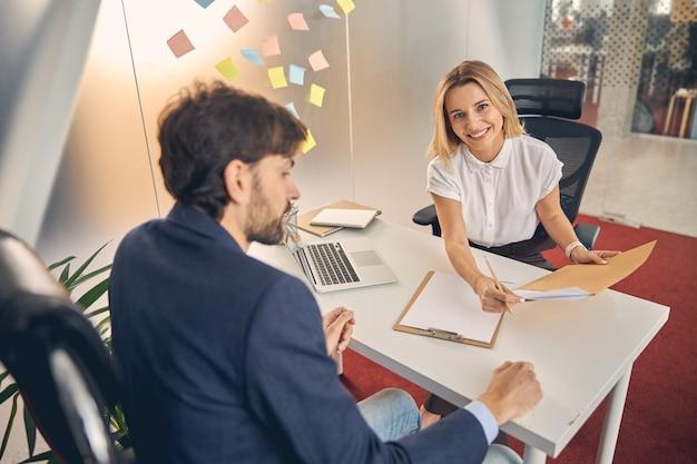 Mooie vrouwelijke werknemer die naar de camera kijkt en glimlacht terwijl ze tegenover de tafel van een bebaarde man zit