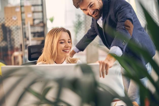 Mooie vrouwelijke werknemer die naar de computer kijkt en glimlacht terwijl een vrolijke man naar het display wijst